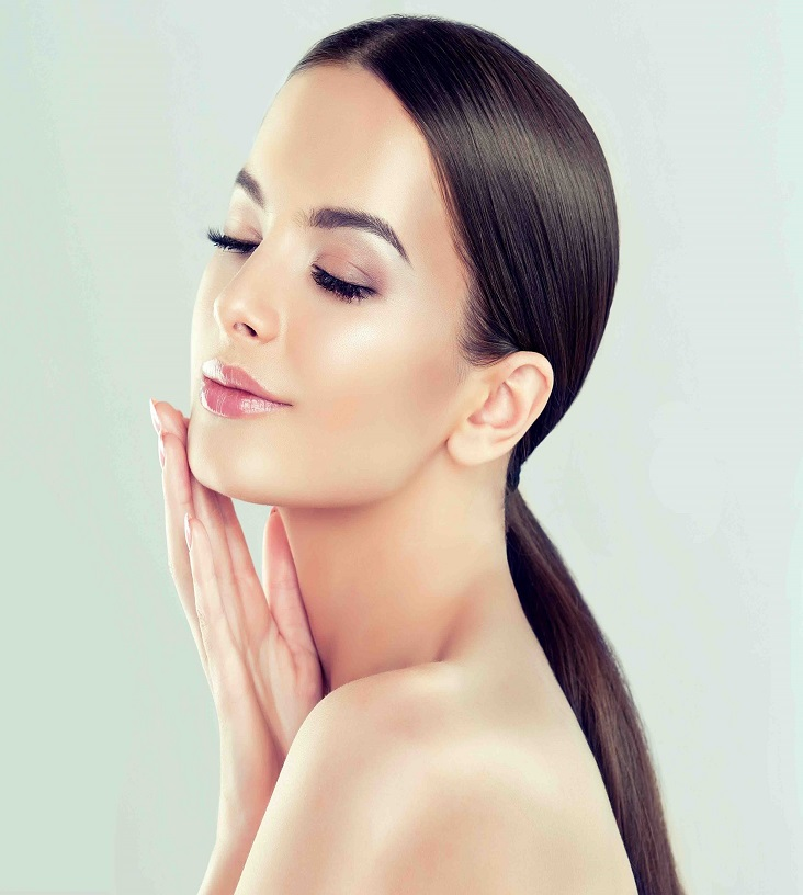 Young  brown-haired woman with clean fresh skin and soft, delicate make up. Woman  is touching own face tenderly. Image of freshness and cleanliness.Cosmetology, plastic surgery,facial treatment and beauty technologies.